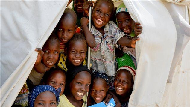 Niños a la entrada de una carpa del Unicef donde asisten a clases y reciben un cuaderno de ejercicios.