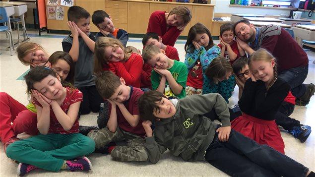 Les élèves de l'école élémentaire catholique Jean-Paul II, leur enseignante Lise-Anne Proulx et Éric Robitaille font une sieste.