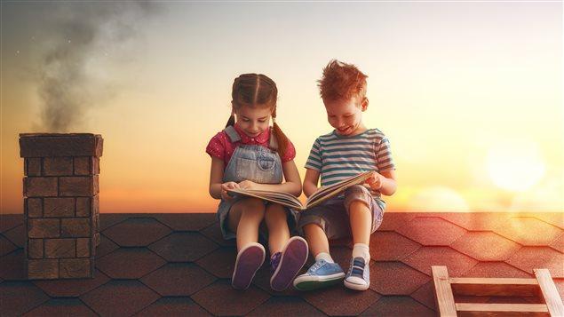 Deux enfants lisent un livre sur le toit d'une maison.