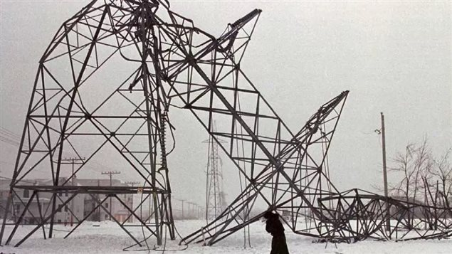 A woman walks past a downed hydro pylon near St-Constant, Que. after one of the worst ice storms to hit Canada struck eastern Ontario and Quebec in January 1998