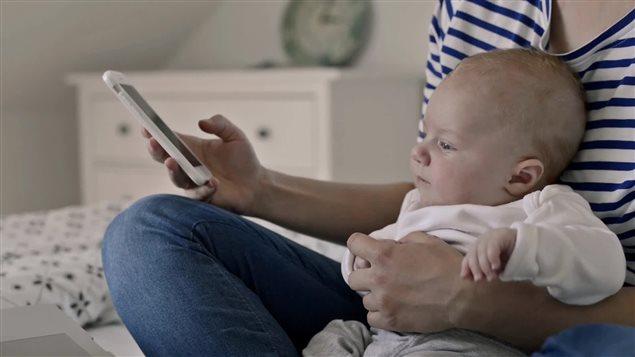 Un enfant dans les bras de sa mère avec un téléphone portable