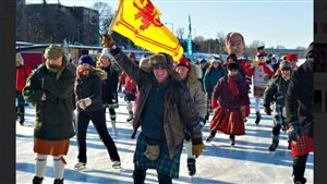 Don Cummer on the Rideau Canal in Ottawa with Royal flag of Scotland in 2015 along with about 200 other kilted skaters, including some members of the Cameron Highlanders Regiment (Duke of Edinburgh's Own)