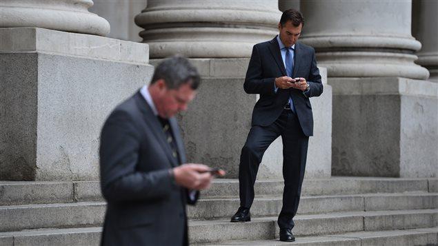 Des hommes d'affaires anglais consultent leur téléphone intelligent.