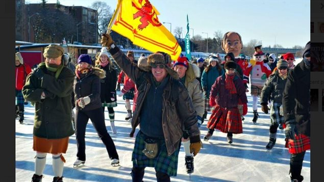 Don Cummer holding the Royal flag of Scotland along with about 200 kilted skaters, including some members of the  Cameron Higlanders Regiment (Duke of Edinburgh's Own) skating at the event on the Rideau Canal, Ottawa, 2015.