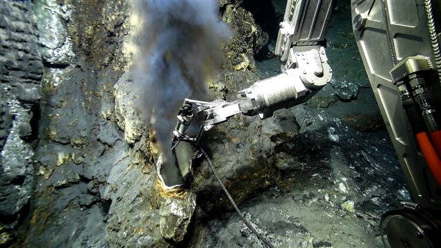 "A temperature gauge is inserted into a ""black smoker"" or hydrothermal vent in the ocean floor to collect data."