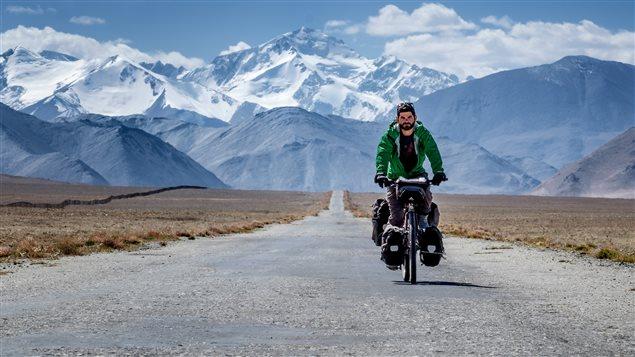 Jonathan B. Roy en vélo avec des montagnes en arrière-plan au Tadjikistan.