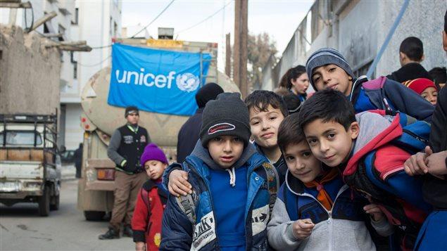 Des enfants posent devant un camion.