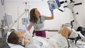 Prof. Michelle Kho monitors a patient on a ventilator as she cycles while lying in bed