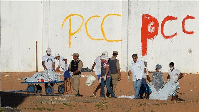 Des corps de détenus tués sont enterré dans la prison d'Alcaçuz, devant le sigle du Premier commando de la capitale (PCC), une puissante organisation criminelle au Brésil.