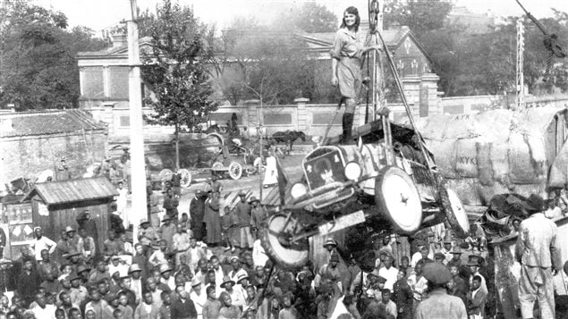 Osaka Japan, 1927. Aloha stands atop one of the cars as ii is loaded aboard ship. The stunt was a crowd pleaser and she would repeat it on other occasions