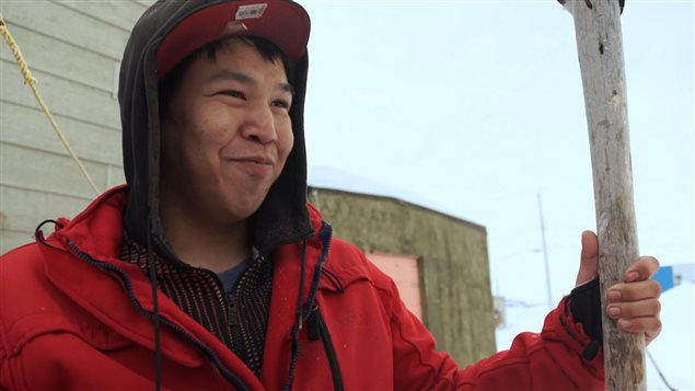 A headshot of a young Inuit hunter holding an ice scoop.