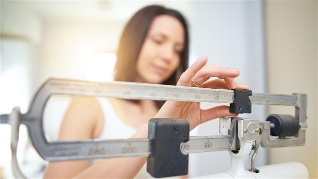 Une femme sur un pèse-personne.