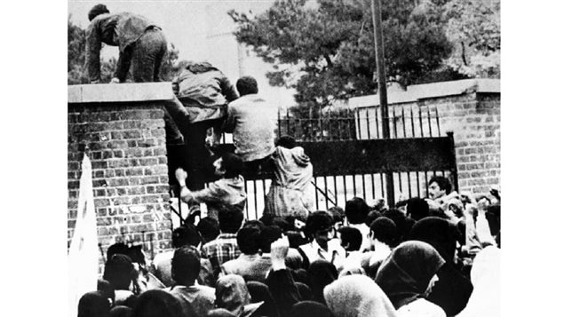 Iranian students climb over the wall of the U.S. embassy in Tehran on Nov. 4, 1979, during the Iranian Revolution. The students went on to seize the embassy staff, and held 52 of them as hostages for 444 days. Taylor was heralded as a hero for helping to save six Americans.