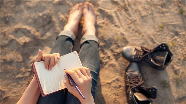 Une femme s'apprête à écrire sur un carnet de notes.