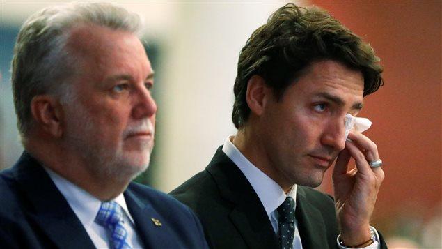 رئيس حكومة كيبك فيليب كويار إلى اليسار وإلى يمينه رئيس الوزراء الكندي جوستان ترودو في مراسم النشييع في كيبك
