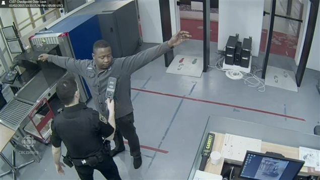 Still photo from internal security video shows Lawrence being checked with a small metal detecting wand after walking through the main metal detector doorway and setting it off. It was later determined the wand was not sensitive enough to detect the gold inside the *body cavity*