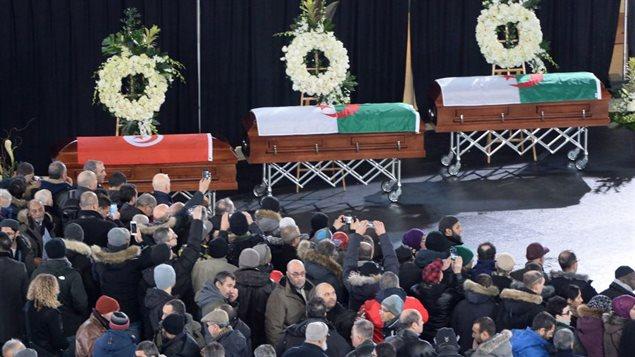 Les cercueils sont entourés de couronnes de fleurs blanches et recouverts du drapeau des pays d'origine des trois victimes, la Tunisie et l'Algérie.Photo: Paul Chiasson La Presse canadienne