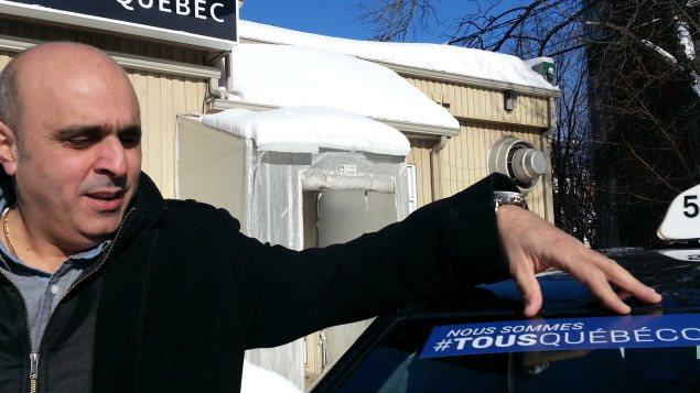 Abdallah Homsy présente un autocollant de la campagne.