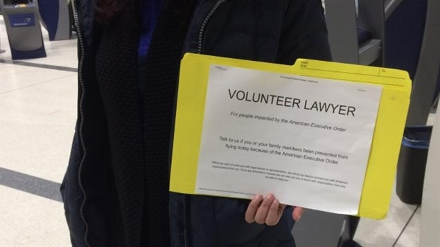 Lawyers  and law students at Canadian airports carry signs offering legal advice to anyone affected by U.S. President Trump's travel order.