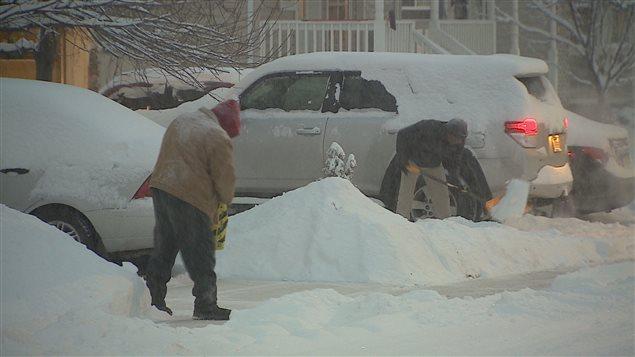 اثنان من سكان كالغاري يجرفان الثلج في فصل الشتاء (أرشيف)