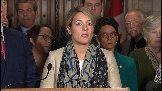 La ministre du Patrimoine canadien, Mélanie Joly, entourée de plusieurs pesonnes pour une annonce devant deux micros.