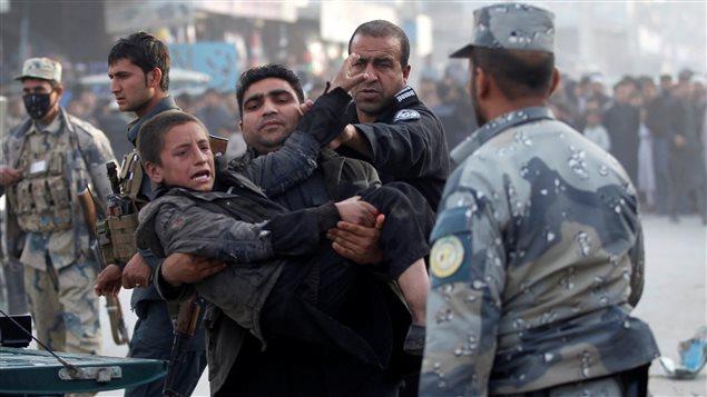Des policiers transportent un garçon blessé après un attentat à Jalalabad, en Afghanistan, février 2017.