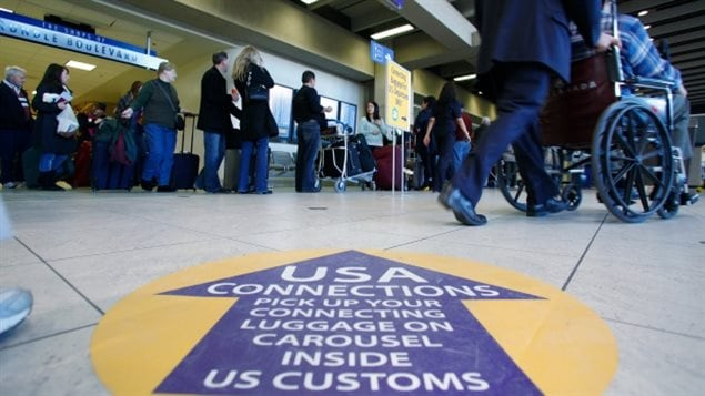 Passengers at Calgary International Airport prepare to clear U.S. Customs and Immigration.