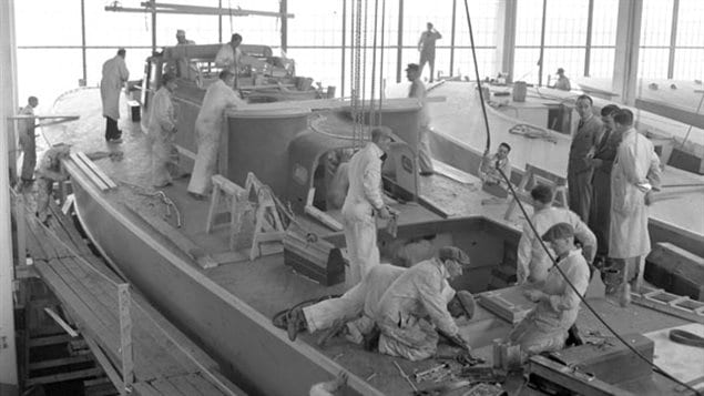 Workers on the deck of an MTB at the Canadian Power Boat Company, Montreal, April 24, 1941. Once the contracts for MTB's and high-speed rescue boats were filled, the company began making wings for Mosquito fighter-bombers.