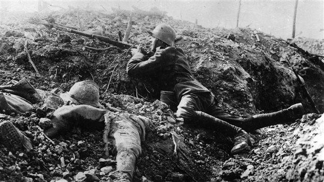 Vers 1916, un soldat allemand tient son arme dans une tranchée à Fort de Vaux, en France, à côté du corps d'un soldat français.