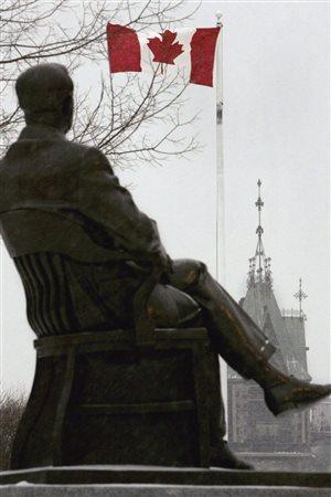 تمثال لرئيس الحكومة الكندية الراحل ليستر بيرسون جالساً وناظراً إلى البرلمان الفدرالي والعلم الكندي يرفرف أمامه، في صورة مأخوذة في شباط (فبراير) 2005 بمناسبة الذكرى الخمسين لولادة العلم الكندي الحالي