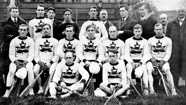 The Canadian lacrosse team at the London Olympics in 1908 with the Maple Leaf (and inset beaver) symbols as background to the word Canada. The maple leaf had already long been a symbol of Canada at international sports events.
