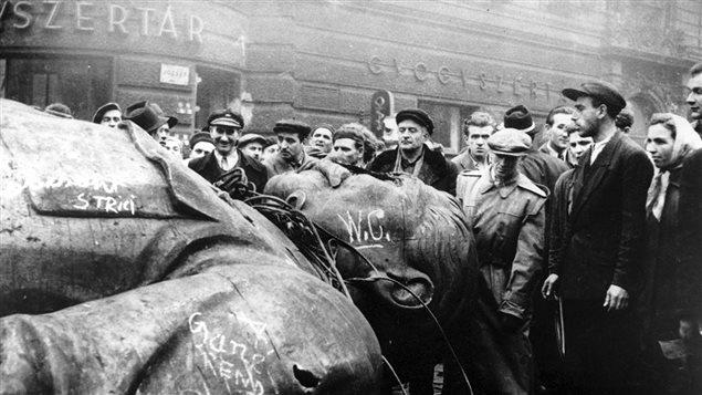 Des révolutionnaires hongrois entourent une statue renversée de Staline devant Théâtre national de Budapest, le 24 octobre 1956.