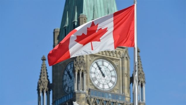 Canada's unique and instantly recognizable Maple Leaf flag in front of the Victory and Peace Tower of Canada's Parliament in Ottawa