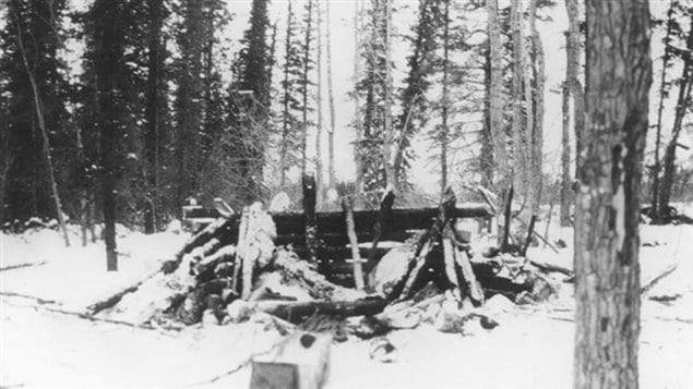The remains of *Johnson's* cabin with only one wall standing  after the RCMP dynamited it. When they approached to pick up his body, he leapt up from a trench he had dug in the floor and fired at them. After a day long shooting standoff, the mounties retreated.