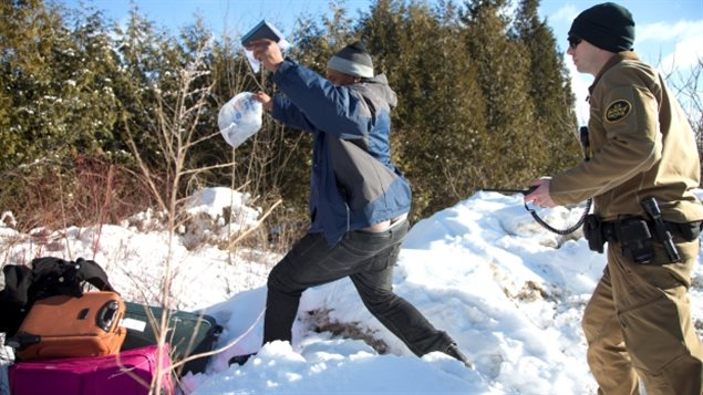 Fri. Feb 18 2017 : A family either from Sudan or Somalia, living in the US for two years dashes across the snow into Canada. Here the father has snattched their passports out of the US border guard's hand and following his family already on the other side is about to leap across the ditch separating Vermont in the US from Quebec Canada.