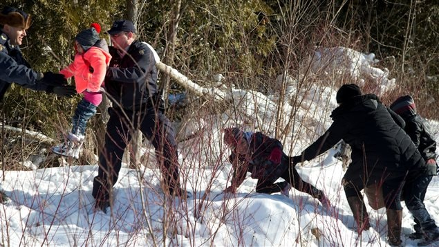 Royal Canadian Mounted Police (RCMP) officers assist a child from a family that claimed to be from Sudan as they walk across the U.S.-Canada border into Hemmingford, Canada, from Champlain in New York.