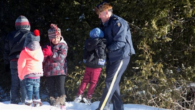 Police officers help undocumented children climb through the snow to cross the border from the United States into Canada.