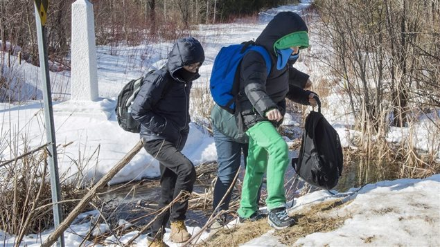 Des migrants en train de traverser la frontière.