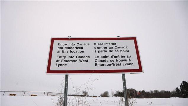 Un panneau situé à proximité d'Emerson, au Manitoba, indique qu'il est interdit de passer la frontière canado-américaine sans passer par un poste frontalier.