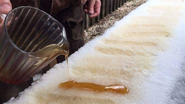 Snow-cooled toffee. Warm maple syrup is poured onto a packed snow surface where the liquid cools to a soft sticky toffee, A popsicle stick/coffee stir stick is then stuck into it and it is lifted from the snow and wound around the stick to create a sort of soft maple toffee lollipop,