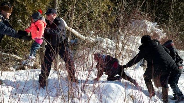 Des agents de la Gendarmerie royale du Canada (GRC) aident un enfant d'une famille qui prétendait être du Soudan alors qu'ils traversent la frontière entre les États-Unis et Hemmingford, au Canada, de Champlain à New York.