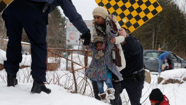 Cette famille soudanaise qui a été arrêtée à Hemmingford, au Québec, au moment où elle tentait de traverser à pied la frontière séparant les deux pays. La femme et ses enfants s'y étaient rendus en taxi (en arrière-plan).