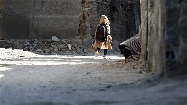 A child carries a school bag near damaged buildings in Harasta, in the eastern Damascus suburb of Ghouta, Syria January 30, 2016. About 1.7 million children are not attending school in Syria because of the war.