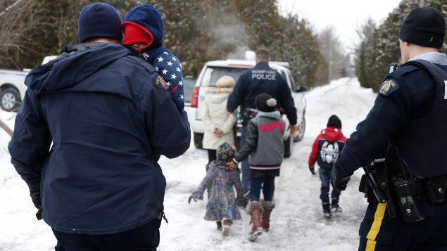 Une famille franchit illégalement à pied la frontière séparant le Canada et les États-Unis.