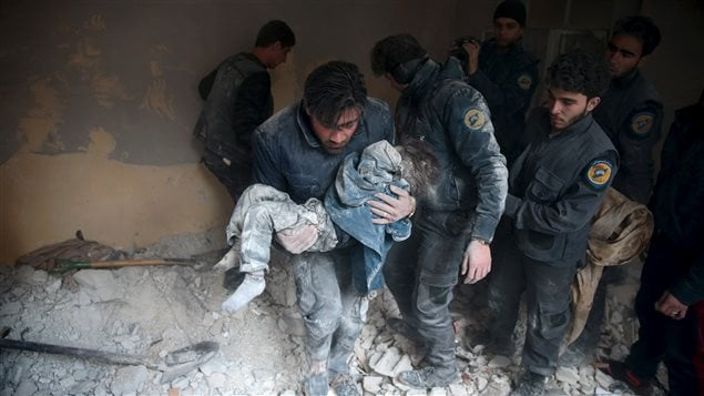 A man carries a child that survived from under debris in a site hit by what activists said were airstrikes carried out by the Russian air force in the town of Douma, eastern Ghouta in Damascus, Syria January 10, 2016.