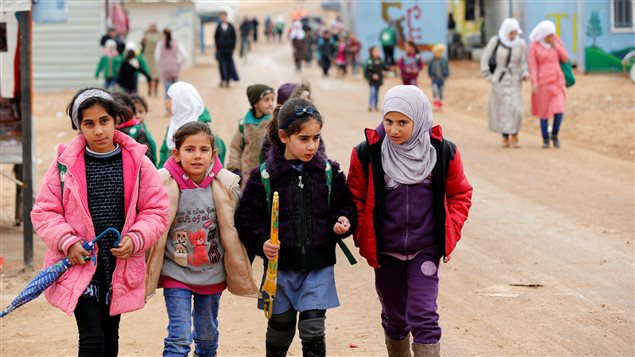 Syrian refugee children walk to the school during rainy weather at the Al Zaatari refugee camp in the Jordanian city of Mafraq, near the border with Syria December 18, 2016.