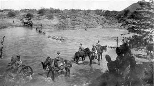 The 2nd (Special Service) Battalion, Royal Canadian Regiment of Infantry crosses the Modder River at Paardeberg Drift on 18 February 1900 to begin the assault on the Boer positions down-river to the east (or right — out of the range of the picture)