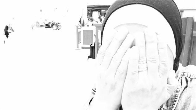 Une femme cache son visage avec ses mains.