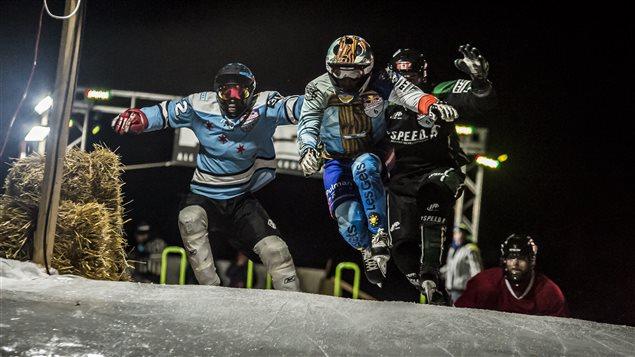 Des athlètes à l'oeuvre lors d'une course de Red Bull Crashed Ice à La Sarre, Canada