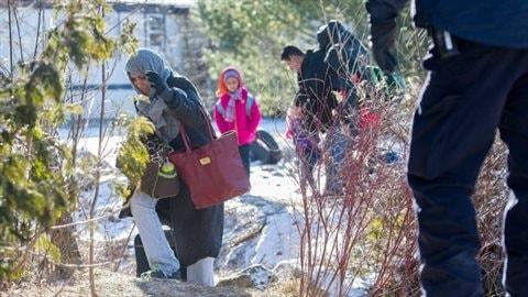 Un agent de la GRC regarde une famille qui prétend être originaire du Yémen traverser la frontière entre les États-Unis et le Canada à Hemmingford (Qc), dimanche. (Graham Hughes / Presse canadienne)